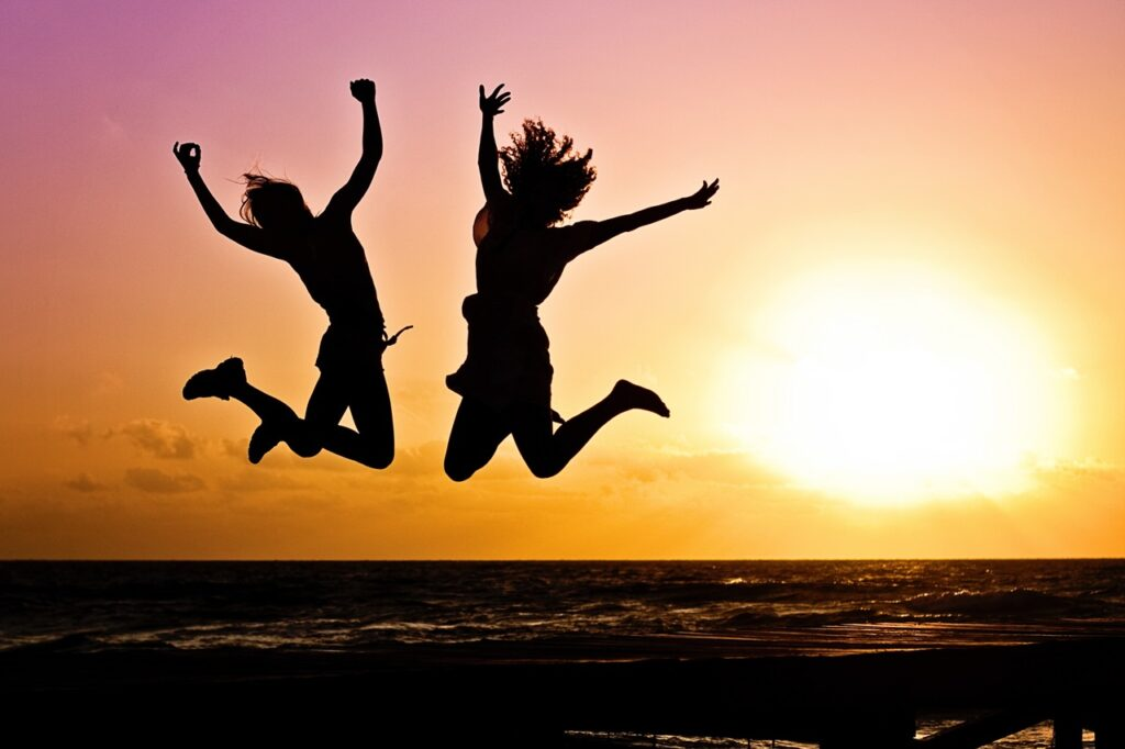 two girls jumping for joy on the beach at sunset