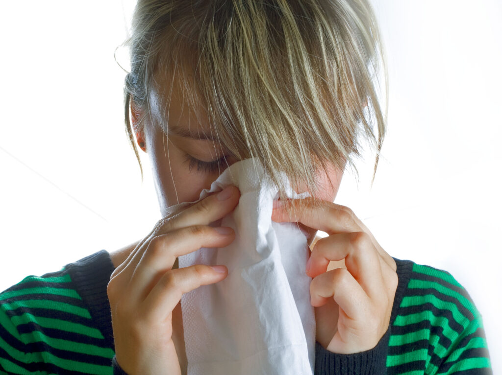 girl with tissue over nose